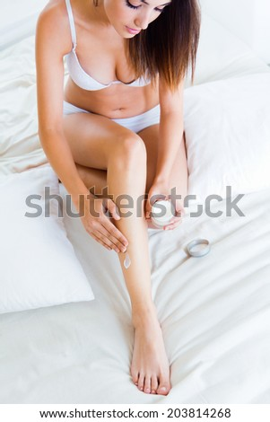 Portrait of beautiful pretty young woman caring about her legs with moisturizing cream - indoors  - stock photo