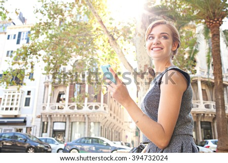 Portrait of beautiful professional young woman using a smart phone working in city with classic buildings outdoors, sunshine flare. Business woman smiling with technology, city lifestyle. - stock photo