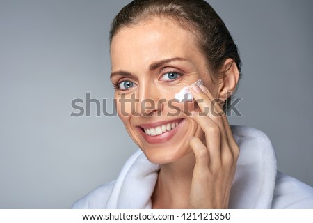 portrait of beautiful radiant mature woman applying some cream to her face, skin care cosmetics wellness concept - stock photo