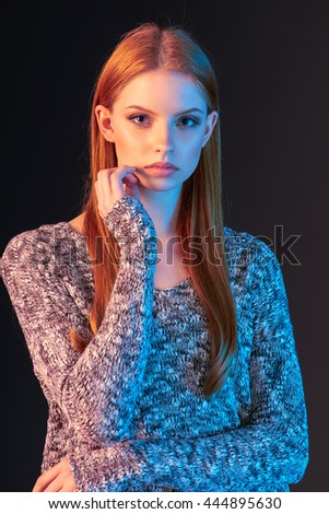 Portrait of beautiful red haired fashion model girl with long hair over dark background, in colorful lighting - stock photo