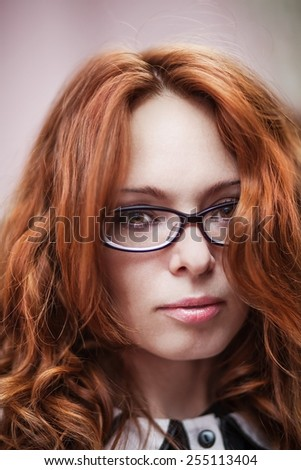 Portrait of beautiful red-haired girl in glasses.