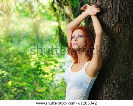 portrait of beautiful red-haired girl posing outdoors around tree's trunk - stock photo