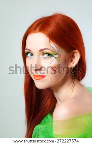 Portrait of beautiful red-haired girl with a flower painted on his face