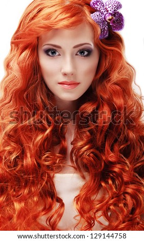 Portrait of beautiful red-haired girl with curly long hair with a flower on a white background. - stock photo