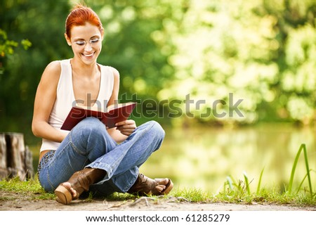 portrait of beautiful red-haired student with book outdoors