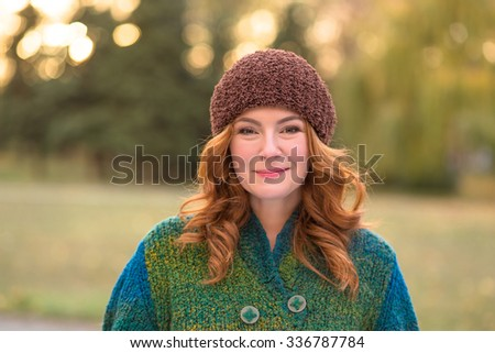 Portrait of beautiful red-haired woman smiling in the park. Happy middle-aged lady with brown hat on walking in the nature.