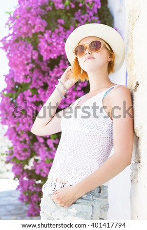 portrait of beautiful redhaired woman standing in shade og blossoming bush - stock photo