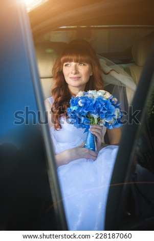 Portrait of beautiful redhead bride sitting at car at sunny day - stock photo