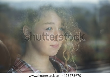 Portrait of Beautiful Redhead Girl Behind Glass with reflection at home - stock photo