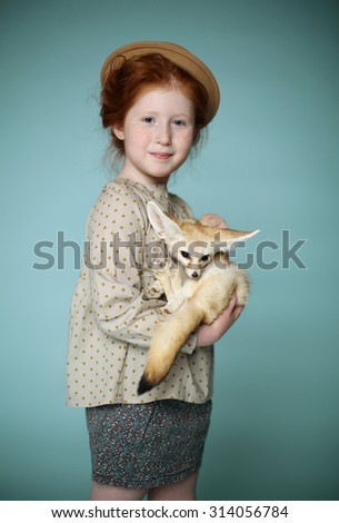 Portrait of beautiful redhead little girl. A Little fox on the hands. Retro style. Studio shot. Blue background  - stock photo