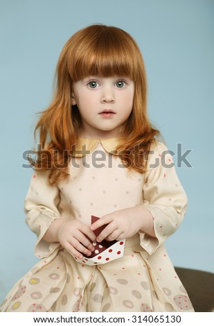 Portrait of beautiful redhead little girl, holding a vintage toy - ship . Blue background. Studio shot - stock photo