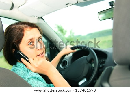 Portrait of beautiful redhead woman driving car  space for inscription - stock photo