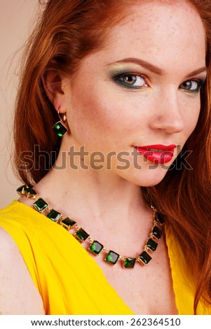 Portrait of beautiful redheaded girl with fashion green jewelry - stock photo
