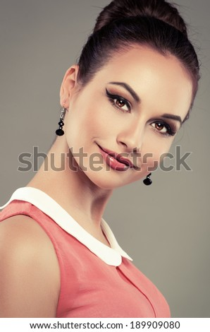 Portrait of beautiful retro girl with professional makeup and salon hairstyle over grey background. Young cheerful Caucasian lady in vintage dress posing in studio.   - stock photo