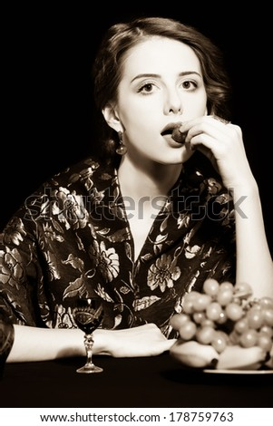 Portrait of beautiful rich women with grapes. Photo in old color image style.