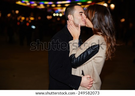 Portrait of beautiful romantic couple embracing at outdoor night event with beautiful lights on background