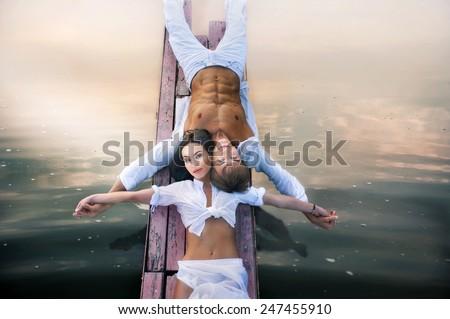 Portrait of beautiful romantic couple on the beach at sunset - stock photo