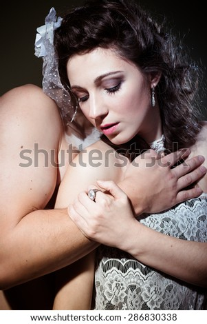 Portrait of beautiful romantic couple with eyes closed hugging on light background