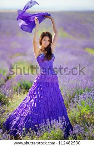 Portrait of beautiful romantic woman in fairy field of lavender - stock photo