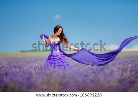 Portrait of beautiful romantic woman in fairy field of lavender with a colored tissue - stock photo