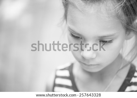 Portrait of beautiful sad little girl close-up. Black and white photo. - stock photo