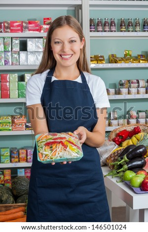 Portrait of beautiful saleswoman holding vegetable packet in grocery store - stock photo