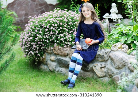 Portrait of Beautiful school girl looking very happy outdoors at the day time. Concept school theme. in blue uniform dress - stock photo