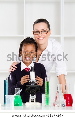 portrait of beautiful science teacher and schoolgirl in lab - stock photo