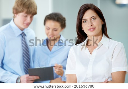 Portrait of beautiful secretary in white shirt looking at camera on the background of co-workers - stock photo