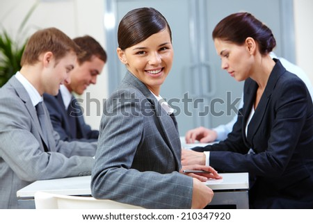 Portrait of beautiful secretary looking at camera on the background of co-workers