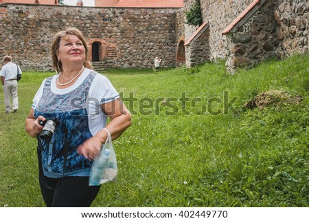 Portrait of beautiful senior blonde woman on the background of the ruins. Attractive senior lady portrait