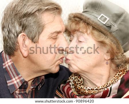 Portrait of beautiful senior couple kissing - stock photo