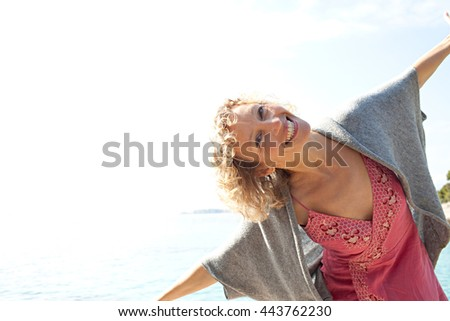 Portrait of beautiful senior tourist woman relaxing with sunny sky on holiday, smiling looking at camera playful with open arms on holiday, coastal outdoors. Healthy lifestyle, nature exterior.