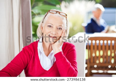 Portrait of beautiful senior woman sitting at nursing home with grandson in background - stock photo