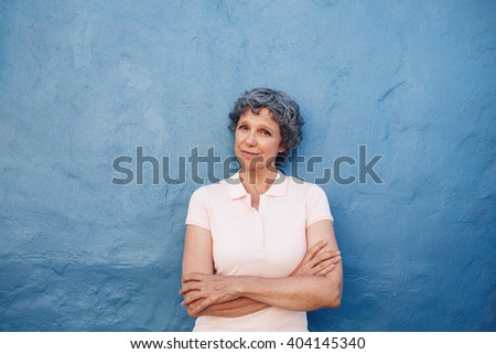 Portrait of beautiful senior woman standing with her arms crossed against blue wall. Happy mature female looking at camera. - stock photo