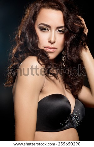 Portrait of beautiful sensual brunette woman with long curly hair