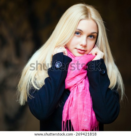 Portrait of beautiful sensual girl with thick blond hair in a black coat and a pink scarf in the fall - stock photo