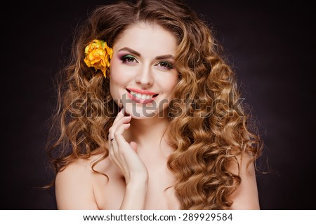 Portrait of beautiful sensual redhead girl with flowers tulips in curly hair, happily smiling in Studio on dark background - stock photo