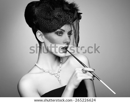 Portrait of beautiful sensual woman with elegant hairstyle.  Woman with cigarette Perfect makeup. Fashion photo. Black and white