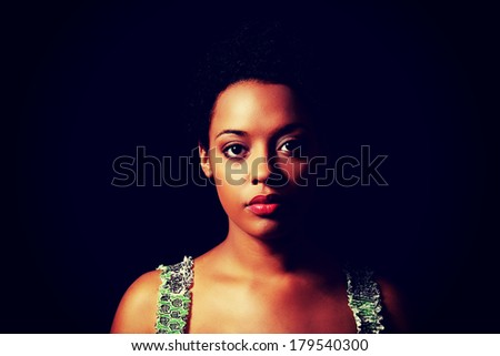 Portrait of beautiful serious afro american woman over black background - stock photo