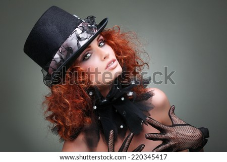 Portrait of beautiful sexual redheaded girl in a black hat on a grey background. Accessories.