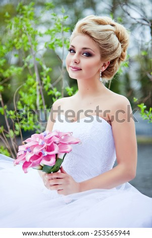 Portrait of beautiful sexy bride blonde in a white dress with purple Calla lilies in his hand, against the background of green leaves - stock photo