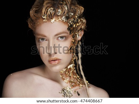Portrait of beautiful sexy fashion model with gold foil on her face