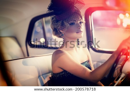 Portrait of beautiful sexy fashion stylish blond girl model with bright makeup in retro style sitting in old car - stock photo
