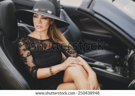 Portrait of beautiful sexy fashion woman model in summer hat and in black dress and luxury accessories with bright makeup sitting in luxury car. Young woman driving on road trip on sunny summer day.