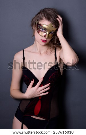 portrait of beautiful sexy woman in lingerie and mask posing over grey background - stock photo