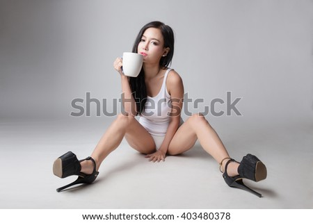 Portrait of beautiful sexy woman in underwear with cup of coffee - stock photo
