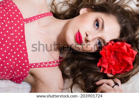 portrait of beautiful sexy young lady brunette pinup girl in polka dot dress having fun sensually looking at camera lying on white bed copy space background closeup image - stock photo