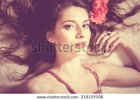 portrait of beautiful sexy young lady brunette pinup girl in polka dot dress having fun sensually looking at camera lying on white bed copy space background, closeup