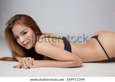 Portrait of beautiful sexy young woman wearing black thong lying on the floor.